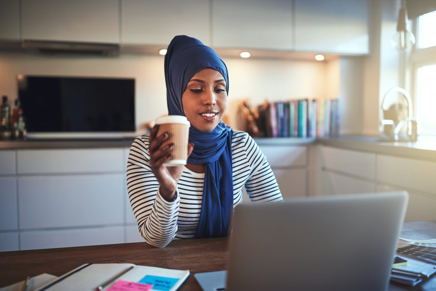 BankingDeal.com - Young Arabic woman drinking coffee and working online at home